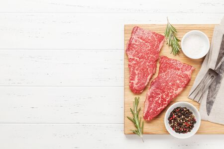 Raw marbled beef steak on wooden board. Top view flat lay with copy space Zdjęcie Seryjne