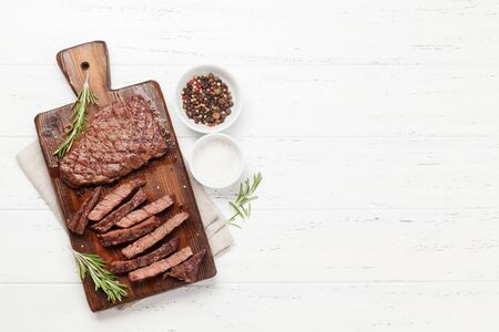 Grilled beef steak on wooden board. Top view flat lay with copy space