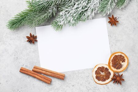 Christmas greeting card with fir tree and spices over stone background and copy space for your xmas greetings. Top view flat lay