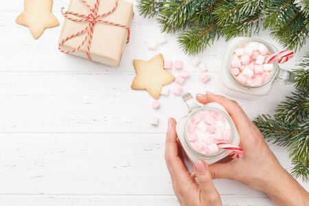 Traditional christmas cocktail with marshmallow. With gingerbread cookies and xmas gift box on wooden table. Flat lay. Top view with space for your greetings Stock Photo