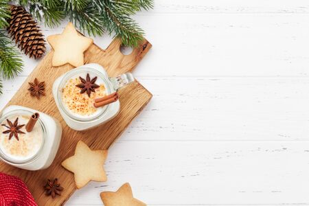 Eggnog. Traditional christmas cocktail and gingerbread cookies on wooden table. Flat lay. Top view with space for your greetings