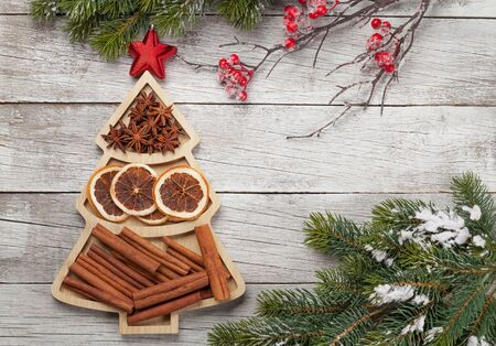 Christmas greeting card with spices in fir tree shaped box and copy space for your greetings. Anise, dry orange and cinnamon. Top view flat lay
