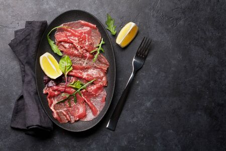 Marbled beef carpaccio with arugula, lemon and pepper. Top view, flat lay with copy space Stock Photo