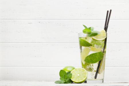 Classic cocktail glass on wooden table. Mojito with lime and mint. With copy space