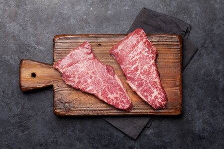 Raw marbled beef steak on wooden board. Top view flat lay with copy space Stock Photo