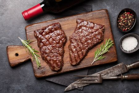 Grilled beef steak on wooden board and red wine. Top view flat lay Stock Photo