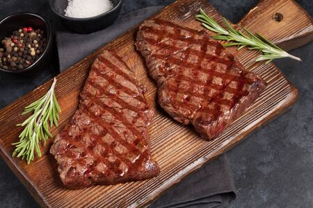 Grilled beef steak on wooden board. Top view