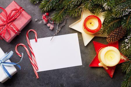 Kerstwenskaart met dennenboom, geschenkdozen en kaarsen op stenen achtergrond. Stockfoto