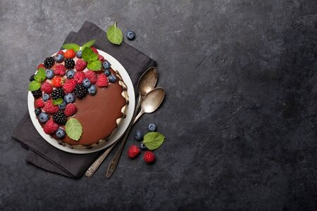 Chocolate cake or cheesecake with berries. On stone table with copy space. Top view flat lay Фото со стока