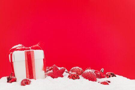 Weihnachtsgrußkarte mit Dekor und Geschenkbox im Schnee über rotem Hintergrund und Kopienraum für Ihre Weihnachtsgrüße