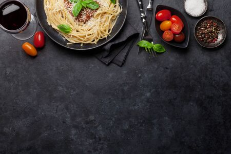 Spaghetti bolognese pasta with tomato and minced meat sauce, parmesan cheese and fresh basil. Red wine glass and cooking ingredients. Top view with copy space