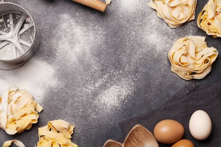 Homemade pasta making on stone table. Top view with copy space. Flat lay