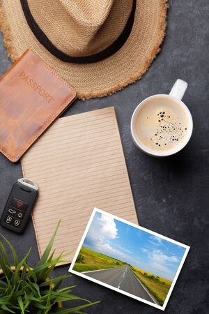 Travel vacation background concept with sun hat, passport, photo and notepad on stone backdrop. Top view with copy space. Flat lay