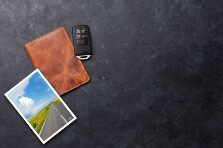 Travel vacation concept with passport, trip photo and car key on stone backdrop. Top view with copy space. Flat lay