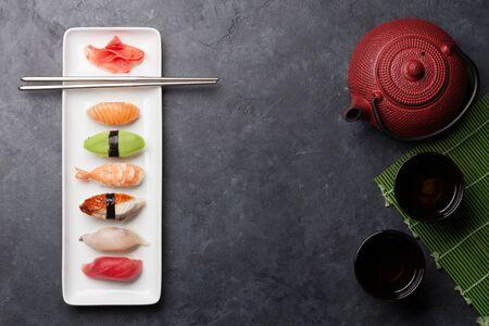 Ensemble de sushis japonais. Sashimi, maki rolls et thé vert. Sur plaque sur fond de pierre avec un espace pour votre texte. Vue de dessus à plat