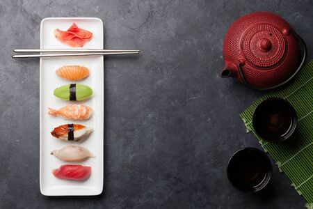 Japanese sushi set. Sashimi, maki rolls and green tea. On plate over stone background with space for your text. Top view flat lay Фото со стока