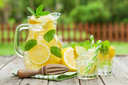 Lemonade with lemon, mint and ice on garden table Stock Photo