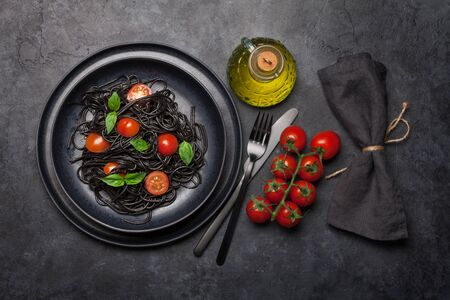 Black spaghetti pasta with tomatoes and basil. Top view flat lay