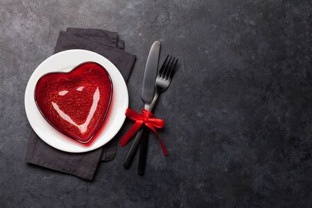 Valentines day or romantic dinner table setting over stone background. Stock Photo