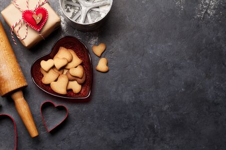 Valentines day gift box and heart shaped gingerbread cookies over stone background with copy space for your greetings. Top view flat lay