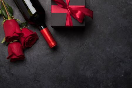 Valentines day greeting card with rose flower bouquet, red wine and gift box over stone background with copy space for your greetings. Top view flat lay