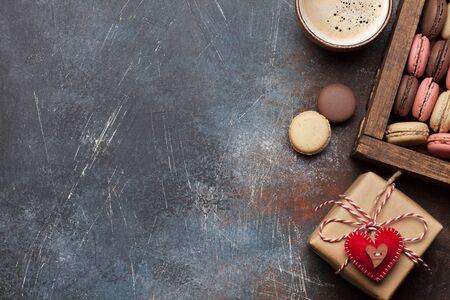 Tarjeta de felicitación del día de San Valentín con caja de regalo, macarrones y taza de café sobre fondo de piedra con espacio para tus saludos. Vista superior plana endecha Foto de archivo