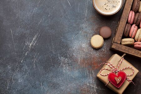 Valentinstag-Grußkarte mit Geschenkbox, Makronen und Kaffeetasse über Steinhintergrund mit Platz für Ihre Grüße. Draufsicht flach legen Standard-Bild