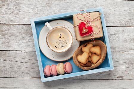 Valentines day greeting box with coffee cup, macaroons and gingerbread cookies over wooden background. Top view flat lay