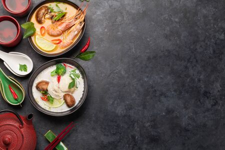 Tom Yum and Tom Kha traditional thai soups with seafood, chicken, mushrooms, coconut milk and hot spices. With green tea in pot and bowls. Top view with copy space