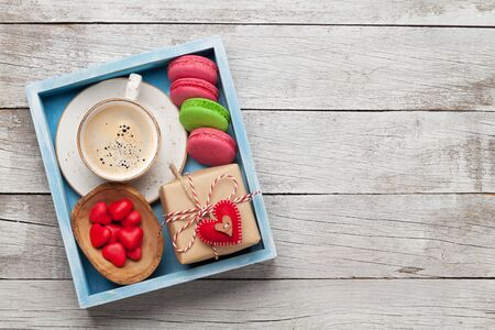Valentines day greeting box with coffee cup, macaroons and gingerbread cookies over wooden background with space for your greetings. Top view flat lay 写真素材