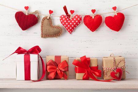 Tarjeta de felicitación del día de San Valentín con corazones hechos a mano y varias cajas de regalo frente a una pared de madera con espacio para copiar tus saludos