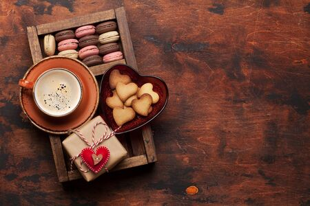 Valentines day greeting card with coffee cup, cookies and gift box on wooden background. Top view flat lay with space for your greetings 写真素材