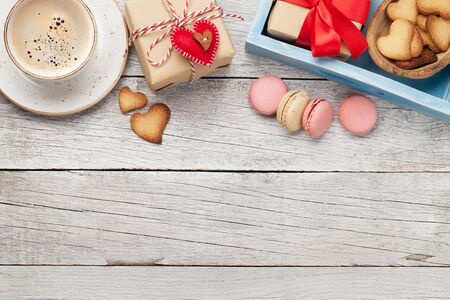 Valentines day greeting card with coffee cup, cookies and gift box on wooden background. Top view flat lay with space for your greetings
