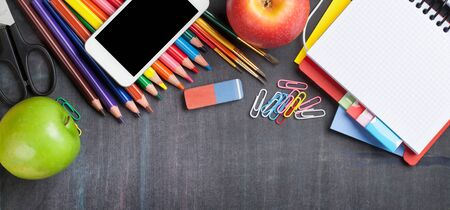 School and office supplies on blackboard background. Top view with copy space. Wide flat lay