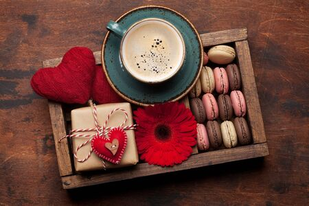 Valentines day greeting card with coffee cup, cookies and gift box on wooden background. Top view flat lay