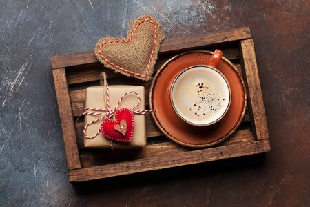 Valentines day greeting card with gift box, handmaded heart and coffee cup in wooden box. Top view flat lay