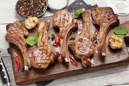 Grilled lamb ribs on cutting board. Hot rack of lamb with spices and condiments Archivio Fotografico