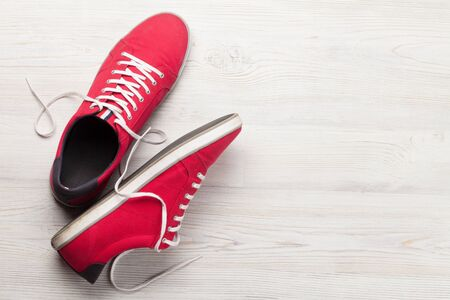 Pair of red sneakers over wooden background with space for your text. Top view flat lay