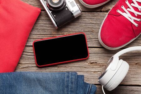 Clothing and accessories. Sneakers, jeans, headphones and smartphone. Urban outfit for everyday or travel vacation on wooden background with copy space on phone screen. Top view flat lay