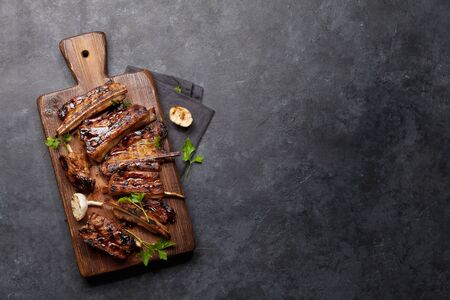 Barbecue beef ribs with bbq sauce sliced on a wooden board. Top view flat lay with copy space