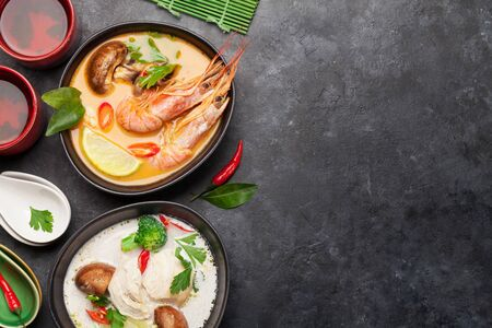 Tom Yum and Tom Kha traditional Thai soups with seafood, chicken, mushrooms, coconut milk and hot spices. With green tea. Top view with copy space