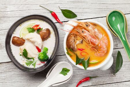 Tom Yum and Tom Kha traditional Thai soups with seafood, chicken, mushrooms, coconut milk and hot spices. Top view
