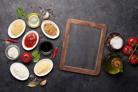 Set of various sauces. Popular sauces in bowls - ketchup, mustard, mayonnaise on dark stone table. Top view with chalk board for your recipe. Flat lay