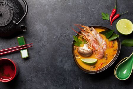 Tom Yum traditional Thai soup with seafood, mushrooms, coconut milk and hot spices. Stock Photo