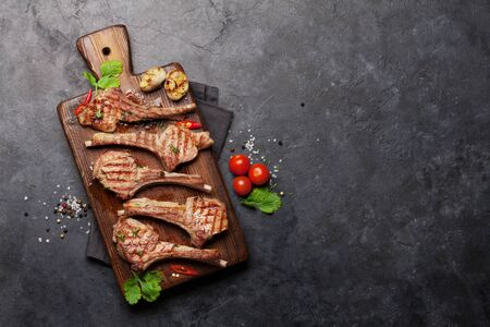 Grilled lamb ribs on cutting board. Hot rack of lamb with spices and condiments. Archivio Fotografico