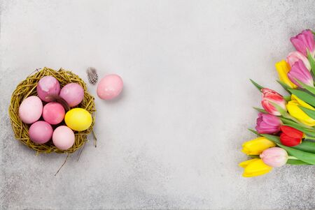Easter greeting card with easter eggs and tulip flowers over wooden background. Top view flat lay with copy space