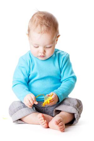 Petit bébé tenant une fleur jaune.