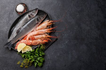 Fresh seafood. Trout fish and langostino shrimps with herbs and spices on a stone background. Top view flat lay. With copy space for your text 写真素材