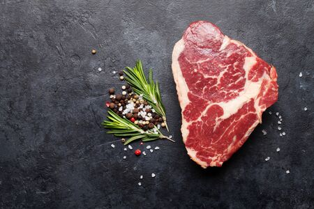 Ribeye fresh raw beef steak with spices on stone board. Top view flat lay with copy space
