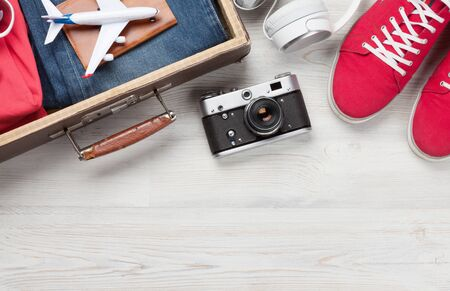Suitcase, camera, clothes and travel accessories. Sneakers, jeans, headphones and camera. Tourist and vacation things on wooden background with space for your text. Top view flat lay